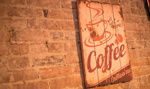 sign on brick wall saying Get More Coffee