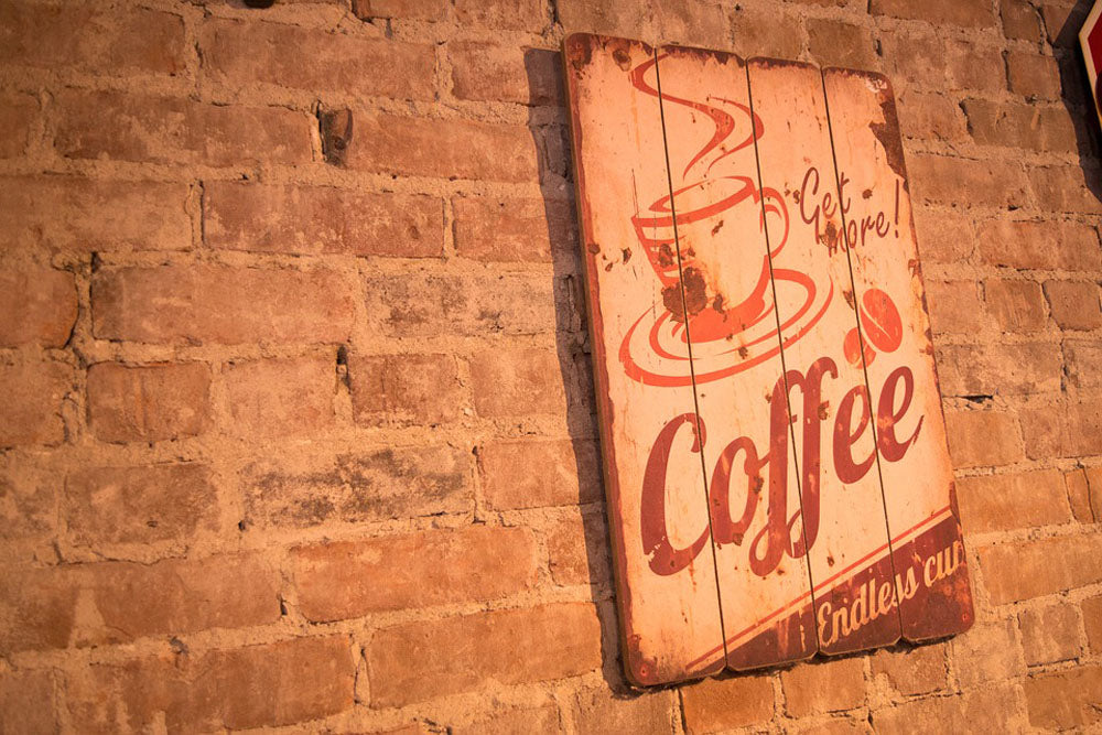 coffee sign that says get more coffee hanging on brick wall