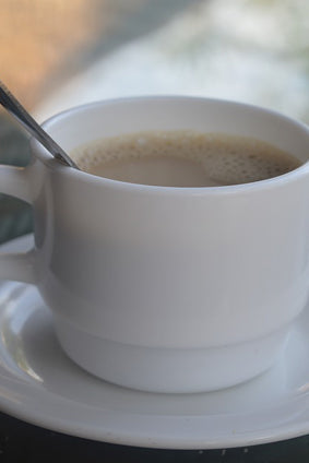 cafe au lait in a white cup with spoon