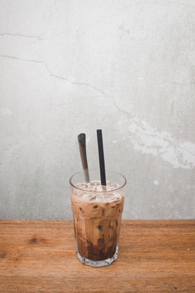 a glass of cold-brew coffee with a spoon and straw