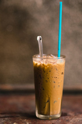frozen iced coffee in glass with spoon and straw