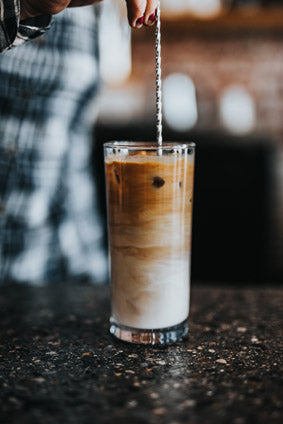 iced coffee in tall glass with straw