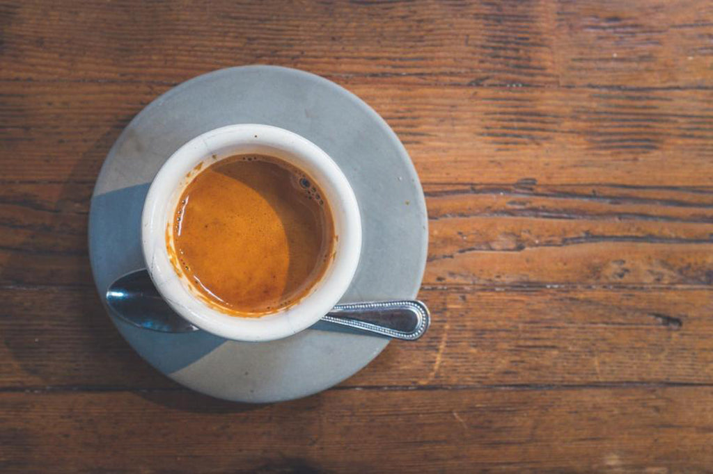 espresso in blue cup on wooden table