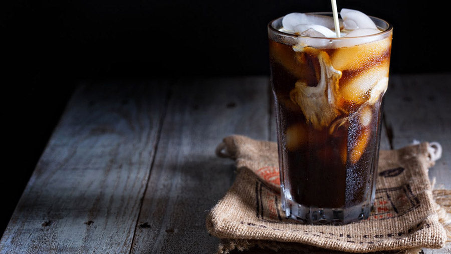 iced coffee in clear glass on small coffee bag