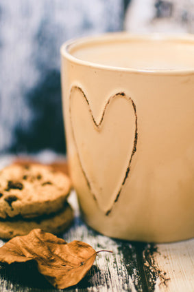 latte in beige cup beside cookies