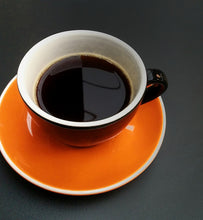 black coffee in an orange and black cup and saucer