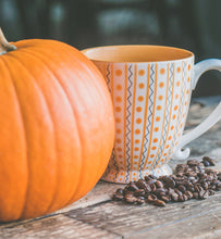 coffee in a blue and orange cup beside a pumpkin