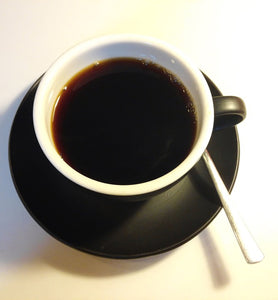 black coffee in a white coffee cup with black saucer