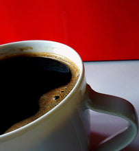 black coffee in white porcelain cup with red background