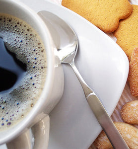 black coffee in white coffee mug beside cookies