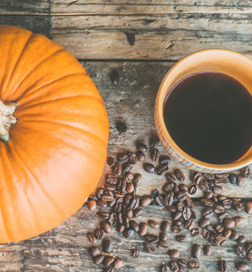black coffee in ceramic cup beside pumpkin and beans