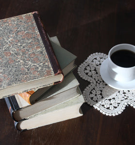 black coffee in white cup beside a stack of books