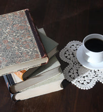 black coffee in white coffee cup beside a stack of books