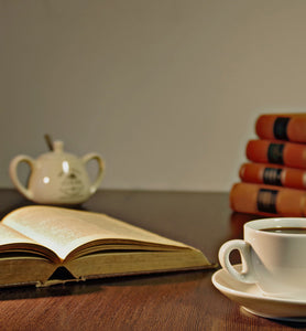 coffee in white coffee cup beside an open book
