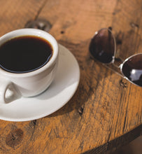 black coffee in white coffee cup beside sunglasses