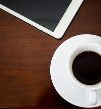 black coffee in white cup beside tablet