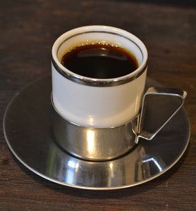 black coffee in stainless steel cup with saucer