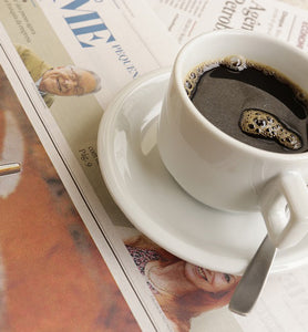black coffee with spoon on Sunday newspaper