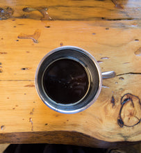 black coffee in silver coffee cup on wooden table