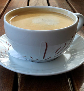 coffee in white porcelain cup with saucer