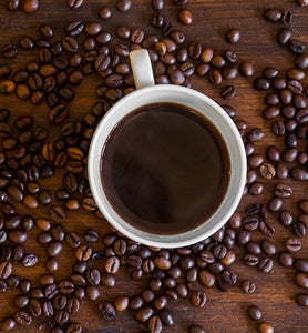 black coffee in white cup surrounded by coffee beans