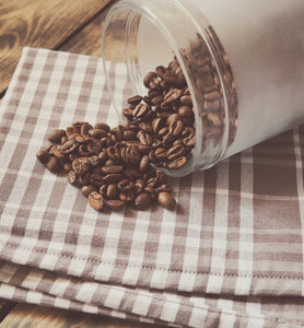 roasted coffee beans spilled from jar onto plaid linen