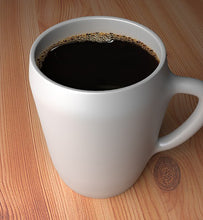 black coffee in white coffee mug on wooden table