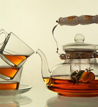 brewed tea in clear glass teapot and three tea cups