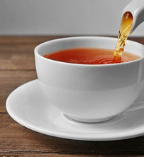Organic English Breakfast Tea pours from kettle into white teacup