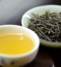 brewed green tea beside green tea leaves