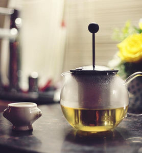 green tea brewing in clear glass teapot
