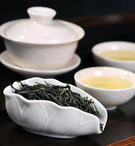 green tea leaves beside two cups of brewed green tea