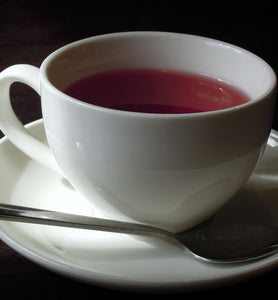herbal tea in white cup with saucer and spoon
