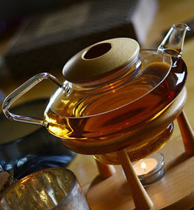 tea infusing in glass tea pot on wooden table