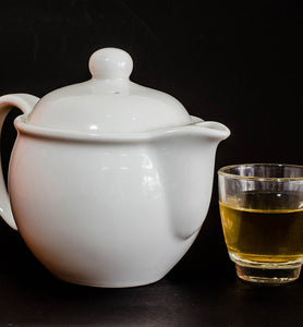 white tea beside white tea kettle