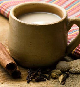 masala chai in brown cup beside spices