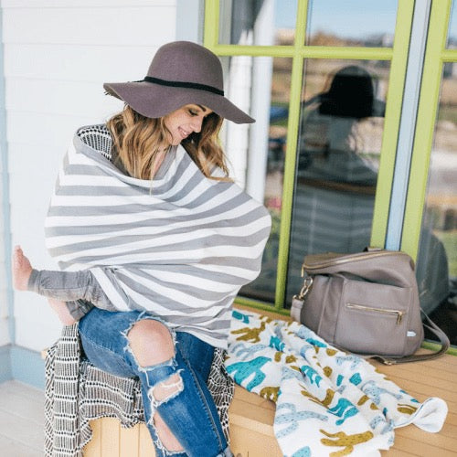 woman nursing a baby in grey stripe nursing cover