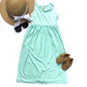 flat lay of mint maxi dress for toddlers sun hat sunglasses and shoes