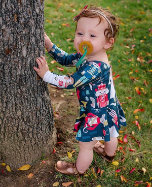 Baby standing in a long sleeve navy blue nutcracker skirted leotard