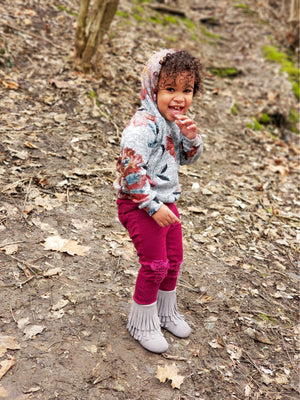 little girl in floral print hoodie exploring the woods cool fashion outfit for toddlers