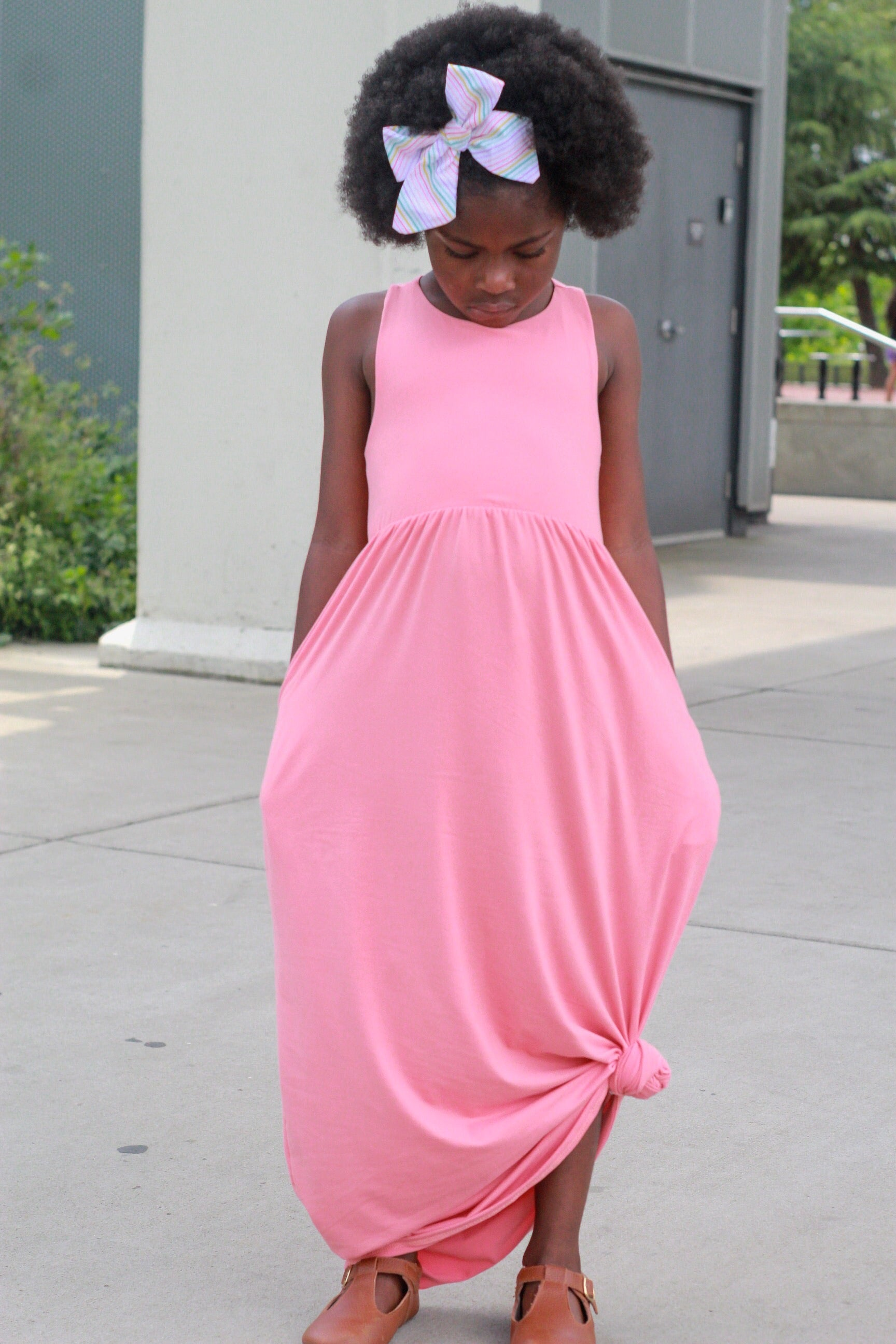 girl standing with her hand in pockets wearing coral maxi dress