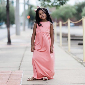 long hair child standing in a sleeveless coral maxi dress