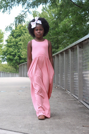 Child with bow standing in a coral sleeveless maxi dress