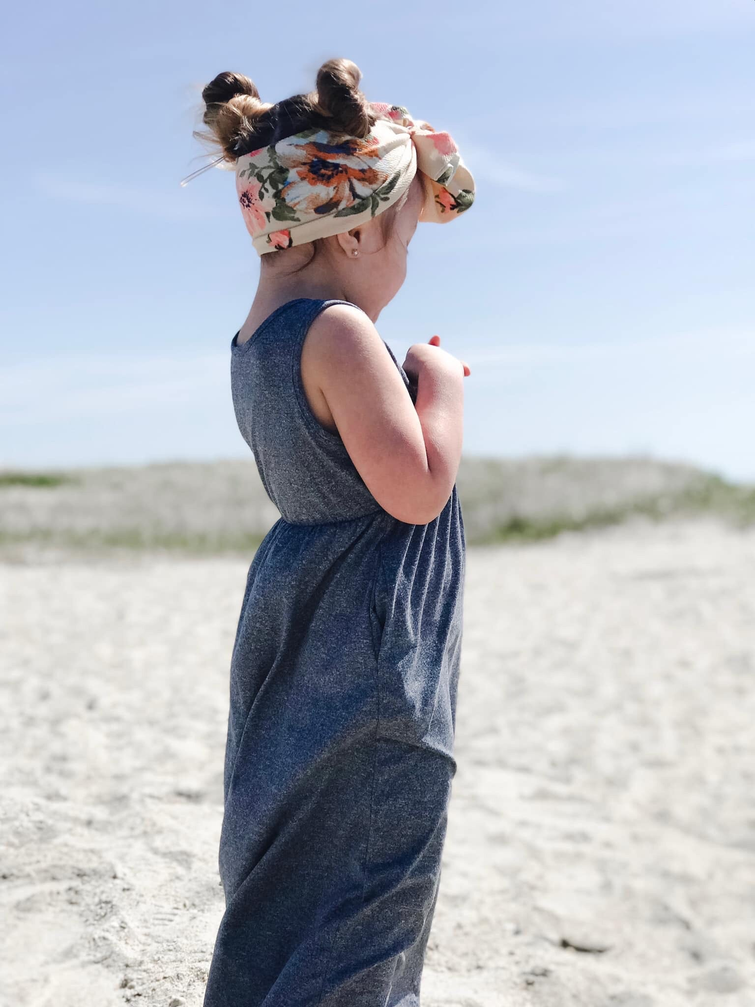little girl at beach standing with floral head wrap wearing denim look maxi dress