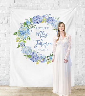 Bride-to-be standing next to hydrangea bridal shower backdrop