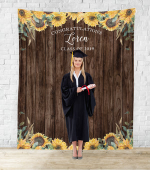 Graduate standing sunflower theme graduation party photo booth backdrop