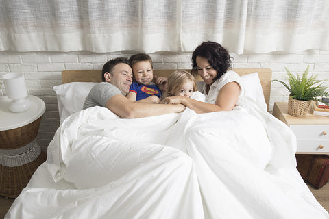 family-cuddle-in-bed-with-duvet