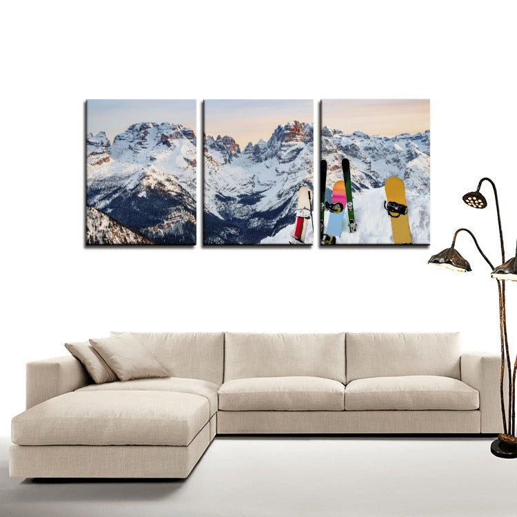 b79cb0ead89 three piece framed canvas wall art of a snowy mountain with snowboards on  the hill.