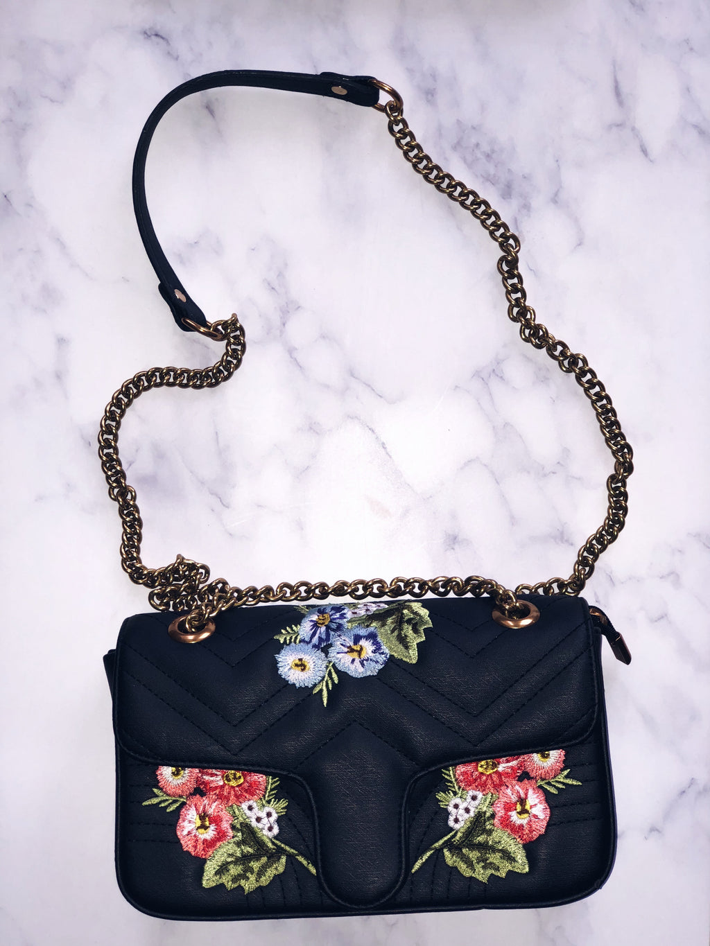 Add this perfect staple to your handbag collection with our La Fleur Cross Body Bag. This purse is embroidered with beautiful spring time flowers and includes a chain linked strap. || This item is final sale. || No exchanges or returns.