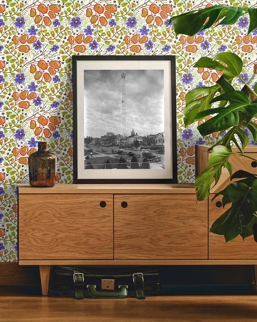 Bright, vivid abstract floral removable wallpaper behind modern credenza with photographs and plants